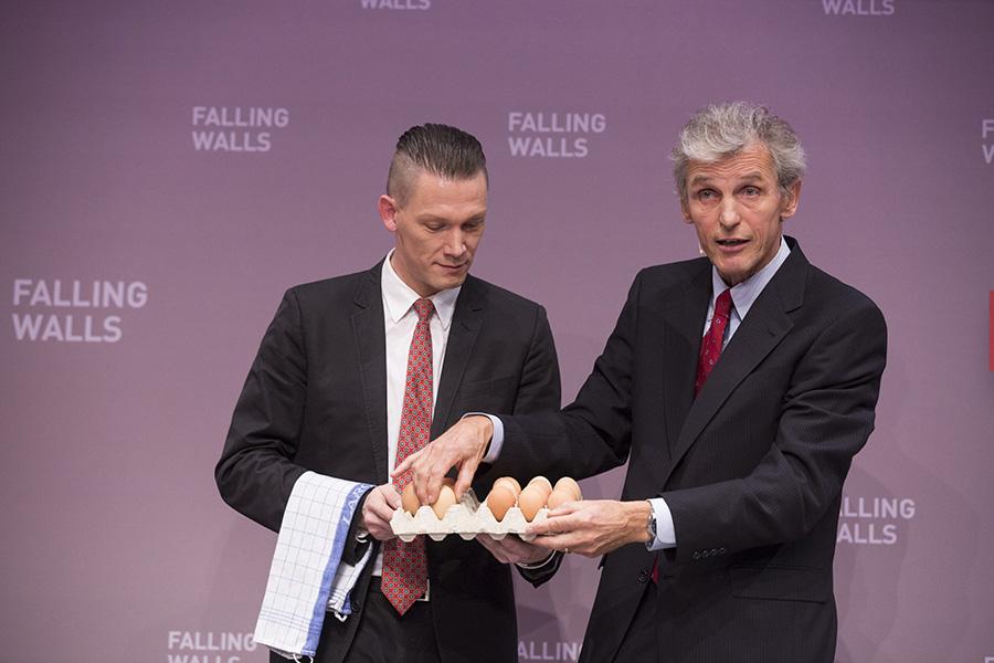"""Wolfgang Ketterle (oikealla) sai Nobelin palkinnon vuonna 2011 """"Bose-Einsteinin kondensaatista"""". Hänen tutkimuksensa koskevat materiaalin olomuodon muutoksia lähellä absoluuttisen nollapistettä. Alustuksessaan hän havainnollisti tutkimuksiaan lego-palikoiden ja kananmunien avulla.  Kuva: Falling Walls Foundation"""