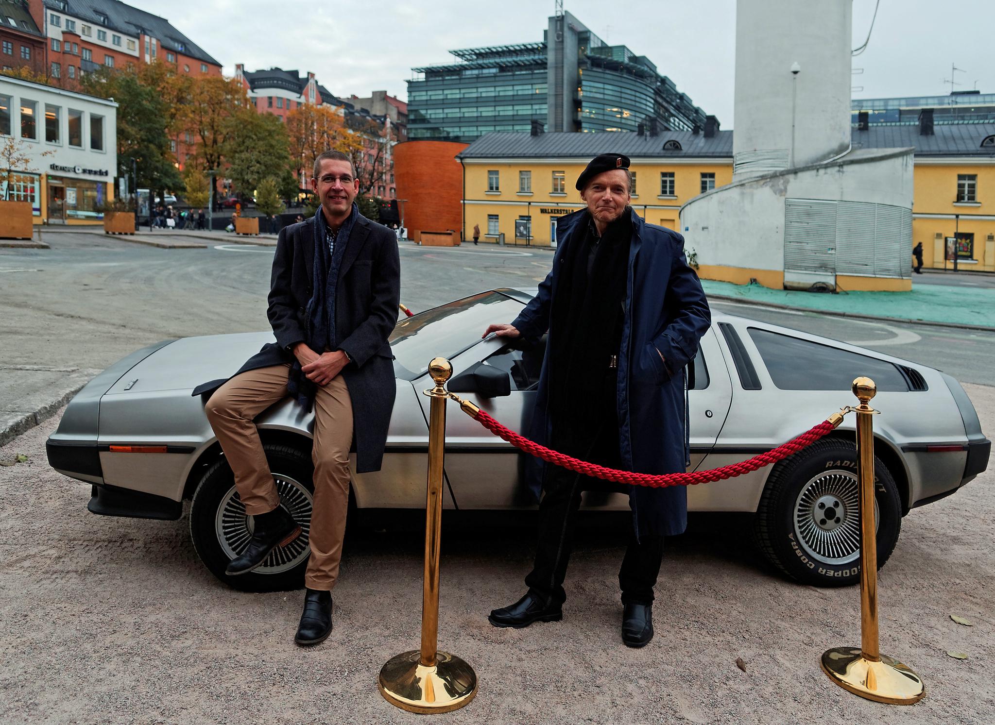 Tiedetoimittaja Jari Mäkinen ja mediatutkija, filosofian tohtori Veijo Hietala keskustelivat Helsingin Bio-Rexissä järjestetyssä Paluu tulevaisuuteen -elokuvatapahtumassa aikamatkustuksesta. Taustalla näkyvä DeLorean DMC-12 -auto edusti Paluu tulevaisuuteen klassikkoelukvatrilogiassa 1980-luvun näkemystä aikakoneesta.