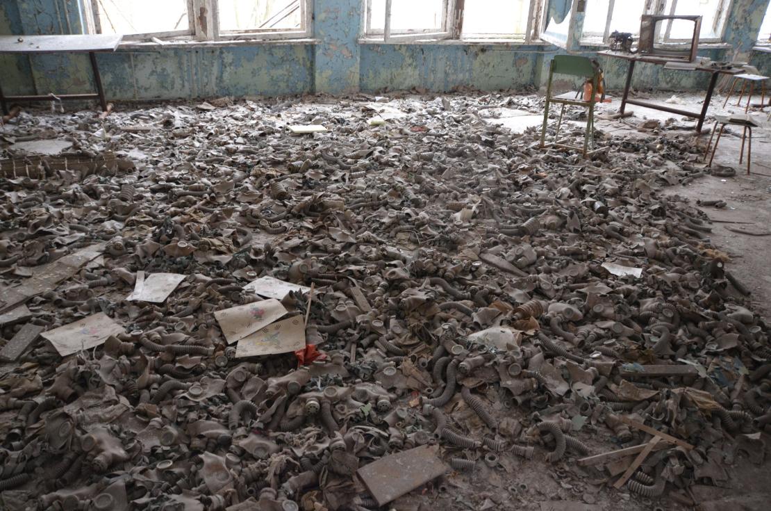Prypjatin koulun lattialle kasattuja suojanaamareita
